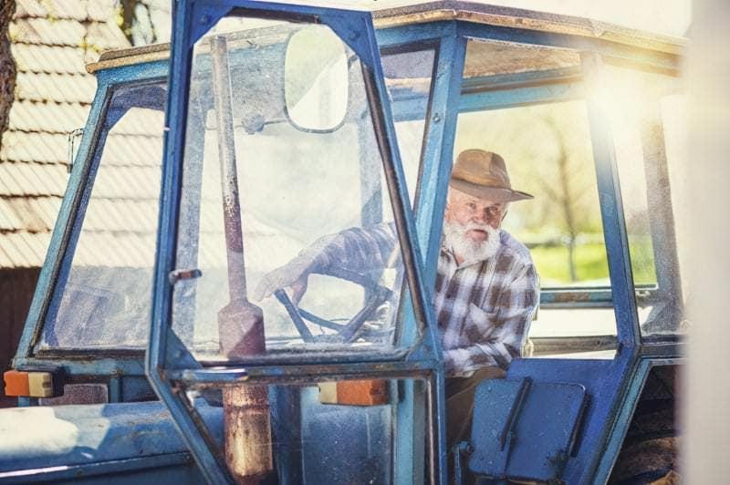 Літній чоловік на тракторі
