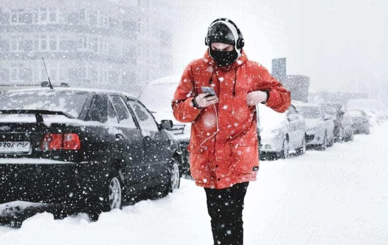 Хлопець йде по сніговій вулиці
