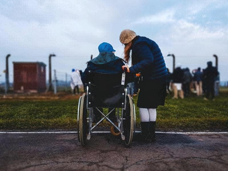 Людина в інвалідному візку і жінка